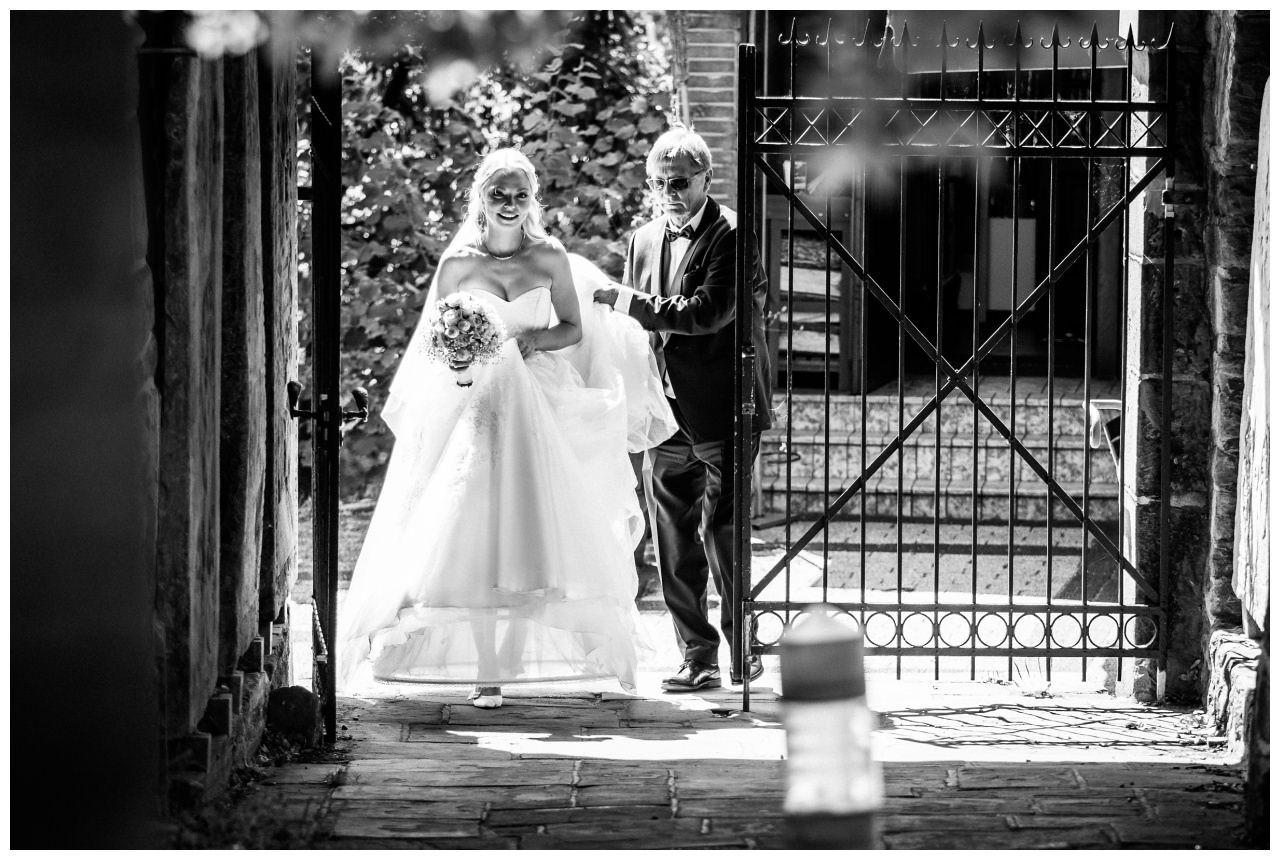 Die Braut kommt mit ihrem Brautvater in den Kirchenhof der Stiepeler Dorfkirche in Bochum.