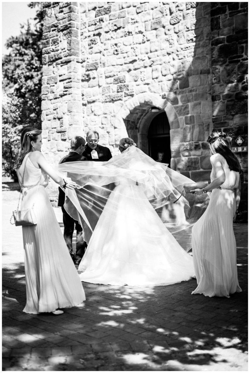 Die Brautjungfern richten den Schleier der Braut kurz vor der kirchlichen Hochzeit vor der Kirche in Bochum.
