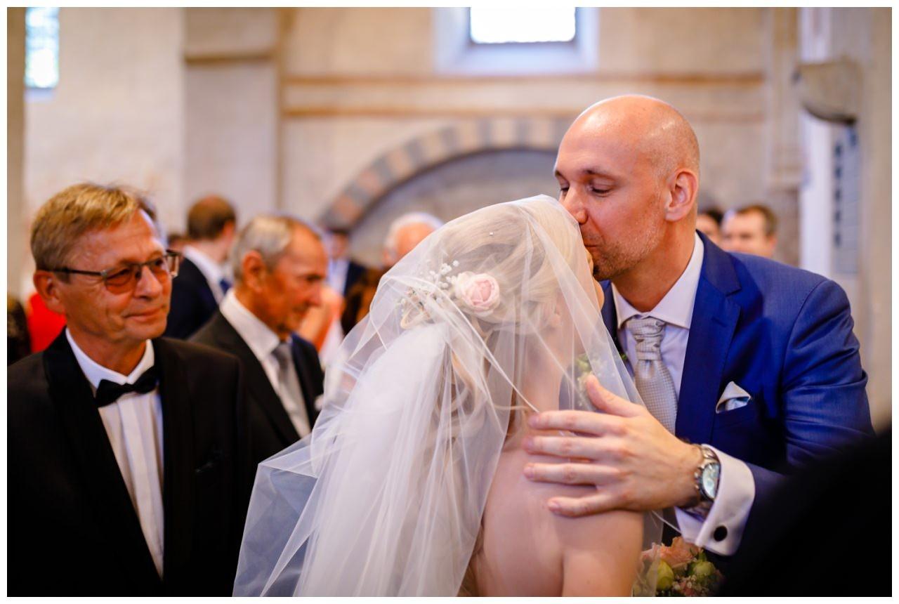 Der Bräutigam küsst seine Braut auf die Stirn bei der kirchlichen Trauung in Bochum Stiepel.