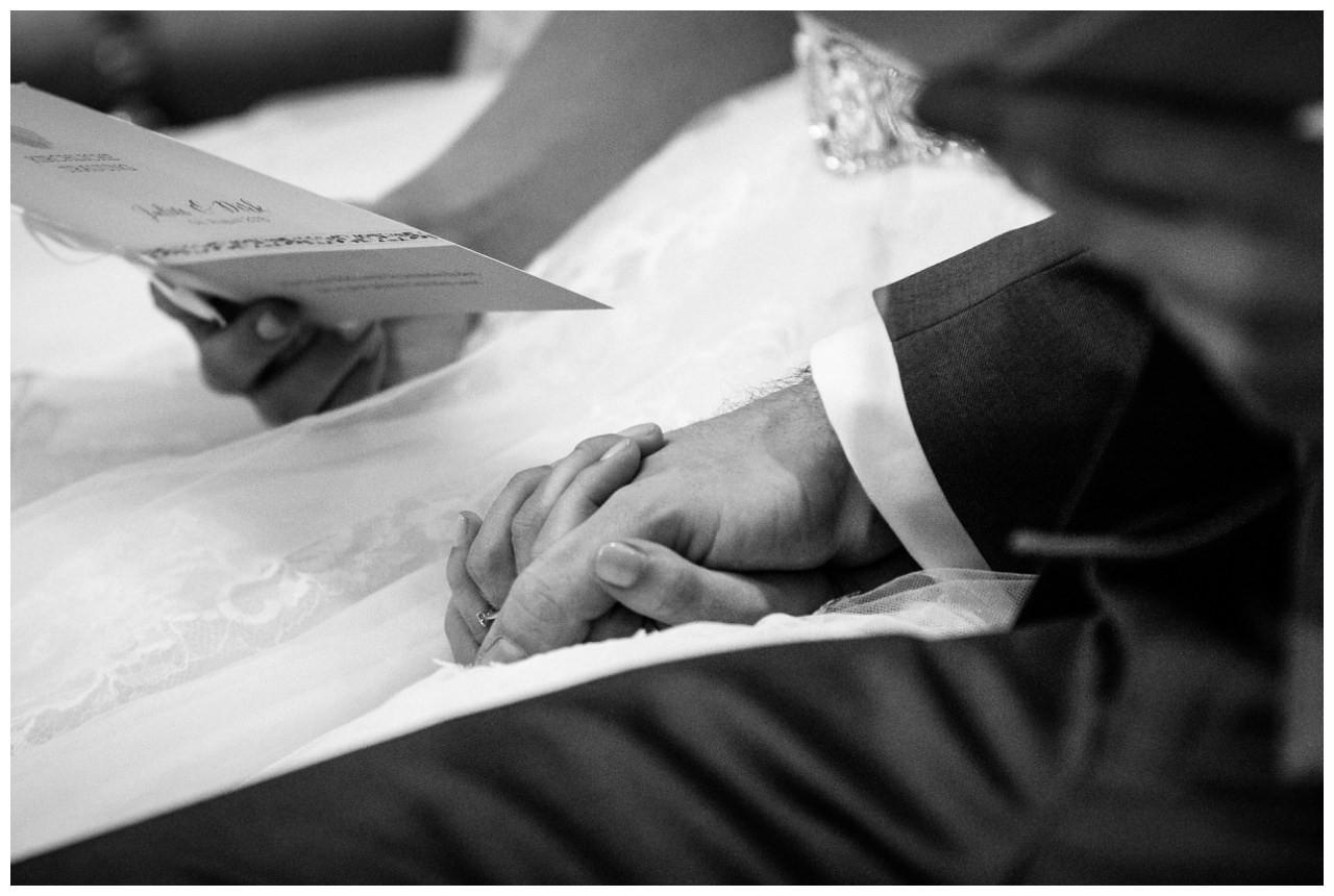 Das Brautpaar hält sich während der kirchlichen Trauung in der Stiepeler Dorfkirche Bochum an den Händen.