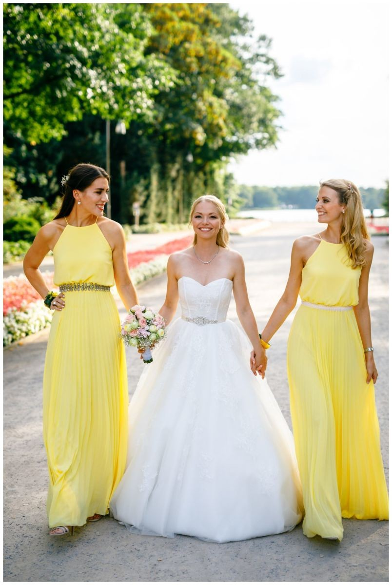 Die Braut mit ihren Brautjungfern in Brautjungfernkleidern in Pastell Gelb.