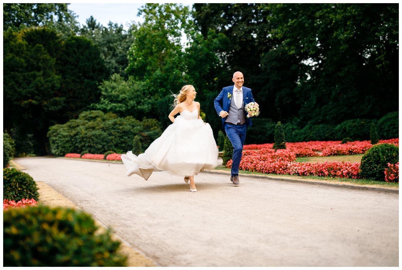 Hochzeitsfoto im Schlosspark von Schloss Berge in gelsenkirchen. Braut und Bräutigam laufen um die Wette.