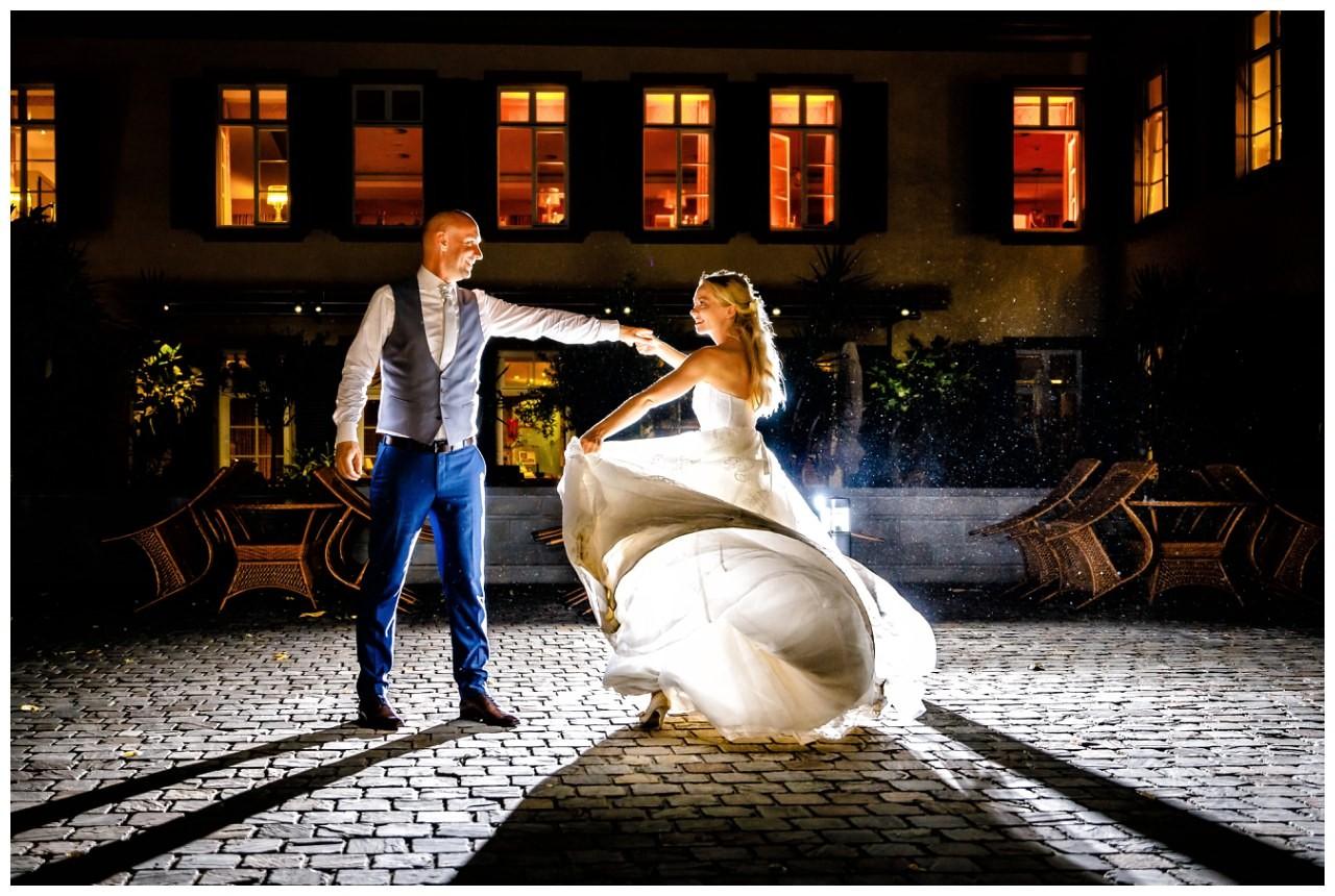Ein Hochzeitsfoto bei Nacht vor Schloss Berge in Gelsenkirchen. Braut und Bräutigam tanzen.