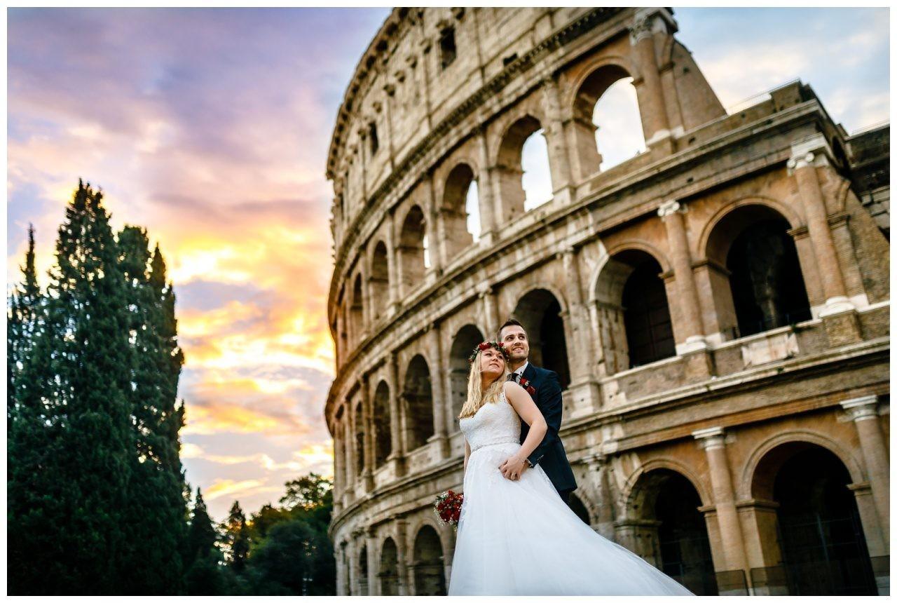 Brautpaarshooting in Rom, das Brautpaar steht vor dem Colosseum.