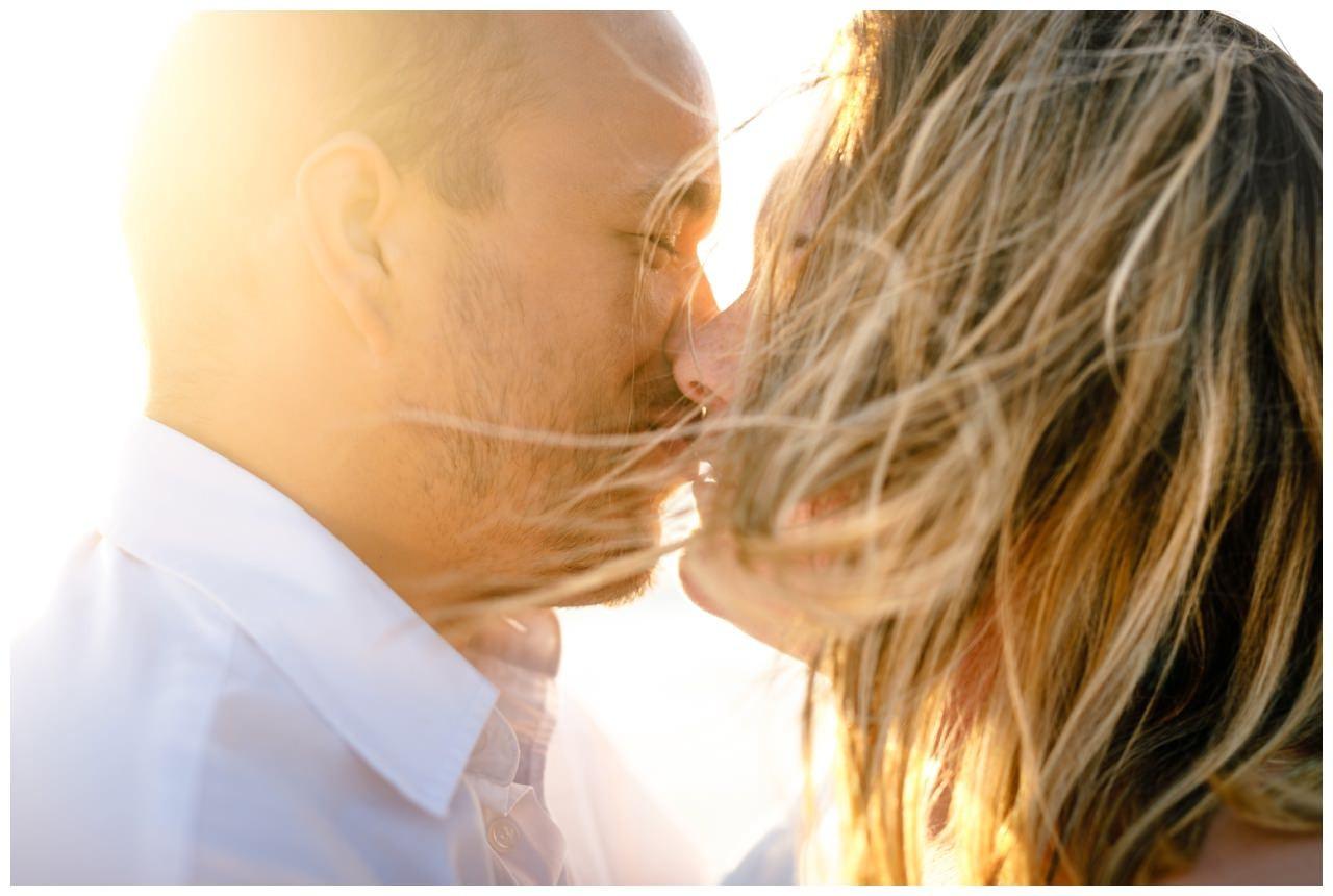Shooting am Strand im Sonnenuntergang von St. Peter ording, das Paar küsst sich und ist in Nahaufnahme zu sehen.