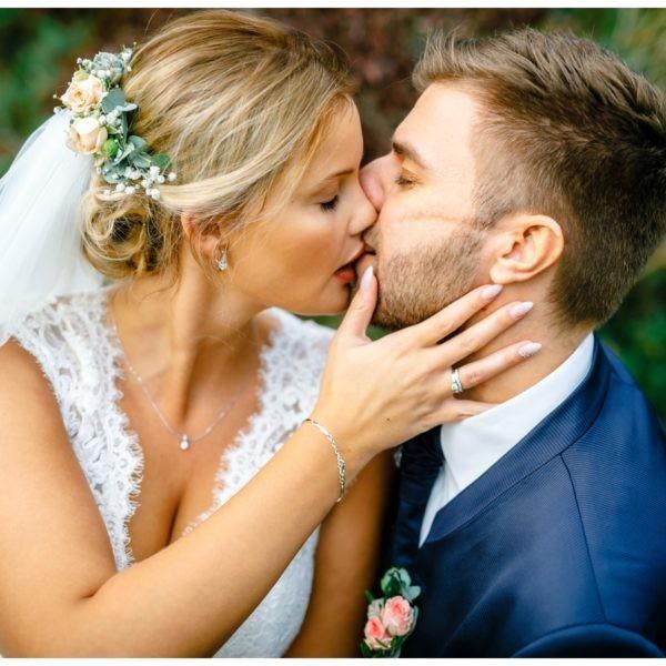 Das Brautpaar küsst sich im Garten von Haus Kemnade.