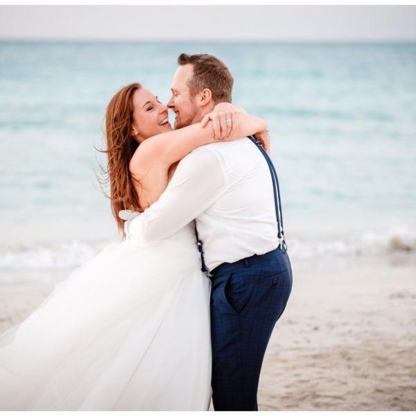 Braut und Bräutigam haben beim After Wedding Shooting am Strand jede Menge Spaß.