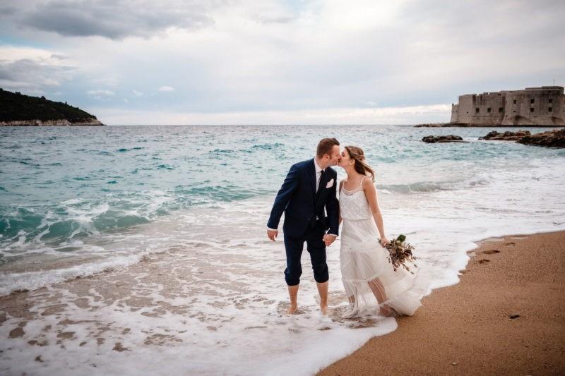 Brautpaar küsst sich am Meer. Im Hintergrund sieht man eine Burg.