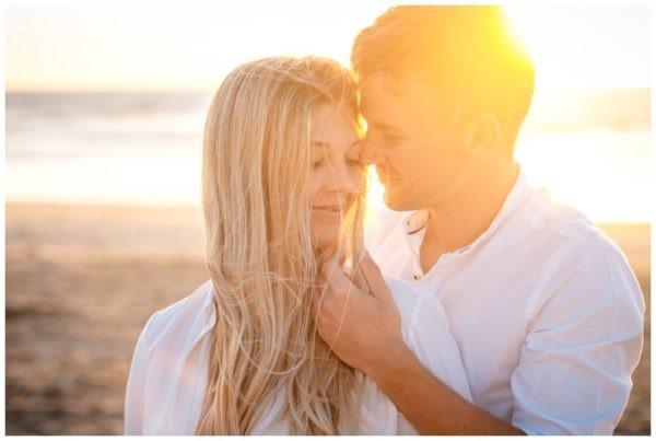 Verlobungsbild am Strand, das Brautpaar kuschelt zärtlich vor dem Hochzeitsfotografen.