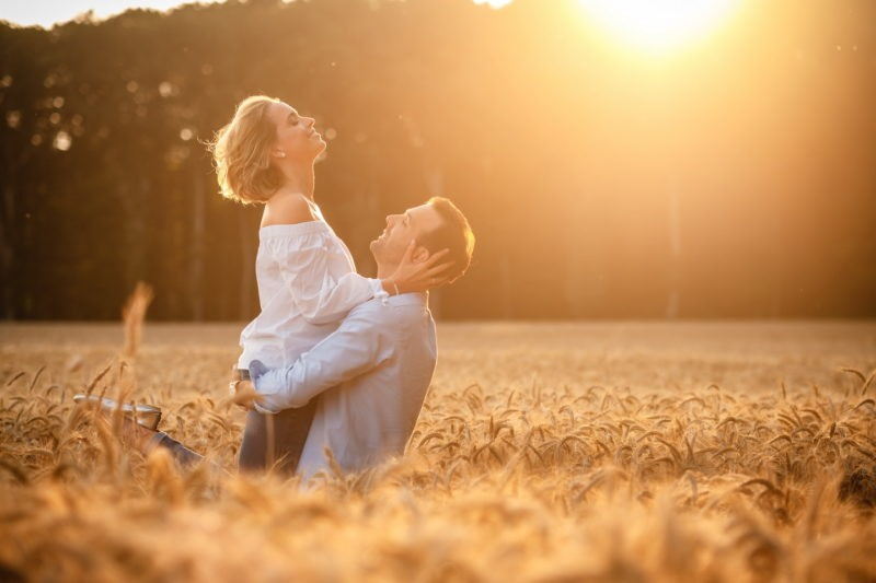 Hochzeitsfotografen Bräutigam hebt Braut hoch Sonnenuntergang im Kornfeld